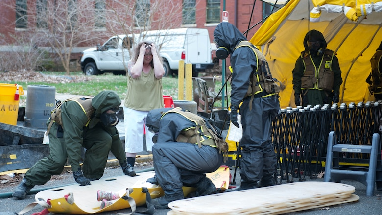 Marines from the decontamination platoon put a child pretending to be injured on a backboard during Exercise Silent Ghost outside St. Elizabeths East hospital in Washington, D.C. April 7, 2015. The exercise was a simulated chemical, biological, radiological, nuclear and high yield explosive incident.
