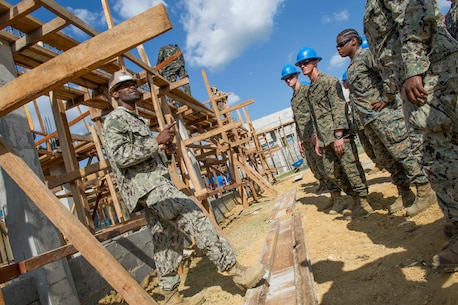 "U.S. Navy Petty Officer 1st Class Andre Dangerfield, left, a construction electrician assigned to Naval Mobile Construction Battalion 5, introduces U.S. Marine engineers and U.S. Navy Seabees to construction at the Don Joaquin Artuz Memorial Elementary School during Balikatan 2015. The Seabees and Marines will join Armed Forces of the Philippines engineers from the 552nd Engineering Construction Battalion, currently at work on the project, in building two classrooms at the school as part of a Combined Joint Civil-Military Operations Task Force on the island of Panay. Balikatan, which means ""shoulder to shoulder"" in Filipino, is an annual bilateral training exercise aimed at improving the ability of Philippine and U.S. military forces to work together during planning, contingency, humanitarian assistance and disaster relief operations."