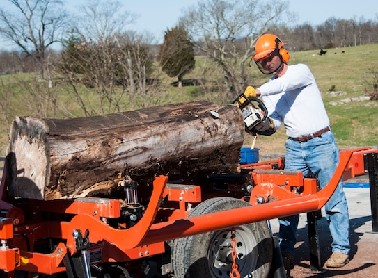 Retired Col. Ronald Light trims a log to better fit the sawmill at Lighthouse Woodworking. April 6.