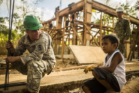 U.S. Army Sgt. Brad Ball, an electrical engineer with the 643rd Engineer Company, 84th Engineer Battalion, 103rd Engineer Brigade, takes a break to speak with a Filipino child at a construction site where Philippine and U.S. engineers are working together to build facilities in the local Puerto Princesa, Philippines, community as part of exercise Balikatan 2015, April 7. This year marks the 31st iteration of the exercise, which is an annual Philippines-U.S. bilateral military training exercise and humanitarian civic assistance engagement.