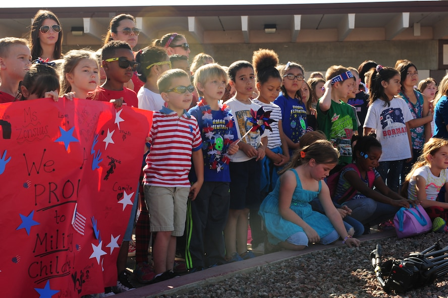 "Students of Borman Elementary School hold a sign saying ""We are proud to be military children,"" during a flag raising ceremony to honor the Month of the Military Child at Davis-Monthan Air Force Base, Ariz., April 10, 2015. April is the Month of the Military Child and on this day the Tucson Unified School District showed their support to the military children by wearing red, white and blue.(U.S. Air Force photo by Airman 1st Class Cheyenne Morigeau/Released)"