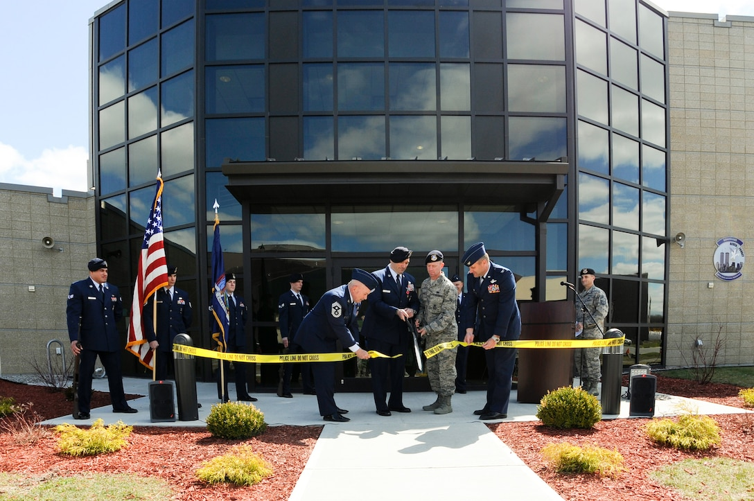 """U.S. Air Force Master Sgt. Todd Lobraico, and Airman 1st Clas, James Byrne, the oldest and newest members of the 105th Base Defense Squadron, New York Air National Guard, cut the ribbon to officially open the 105 BDS Headquarters building with the assistance of Col Timothy J. LaBarge, commander of the 105th Airlift Wing, and Wing Command Chief Master Sgt. Joseph Rizzo . The opening was held shortly after the posthumous award of the Bronze Star Medal with Valor to SSgt. Todd """"T.J."""" Lobraico on April 11, 2015. Lobraico Jr., a member of the 105th Airlift Wing, was killed in action in Afghanistan on Sept. 5, 2013, (U.S. Air National Guard photo by SSgt Michael OHalloran/Released)"""