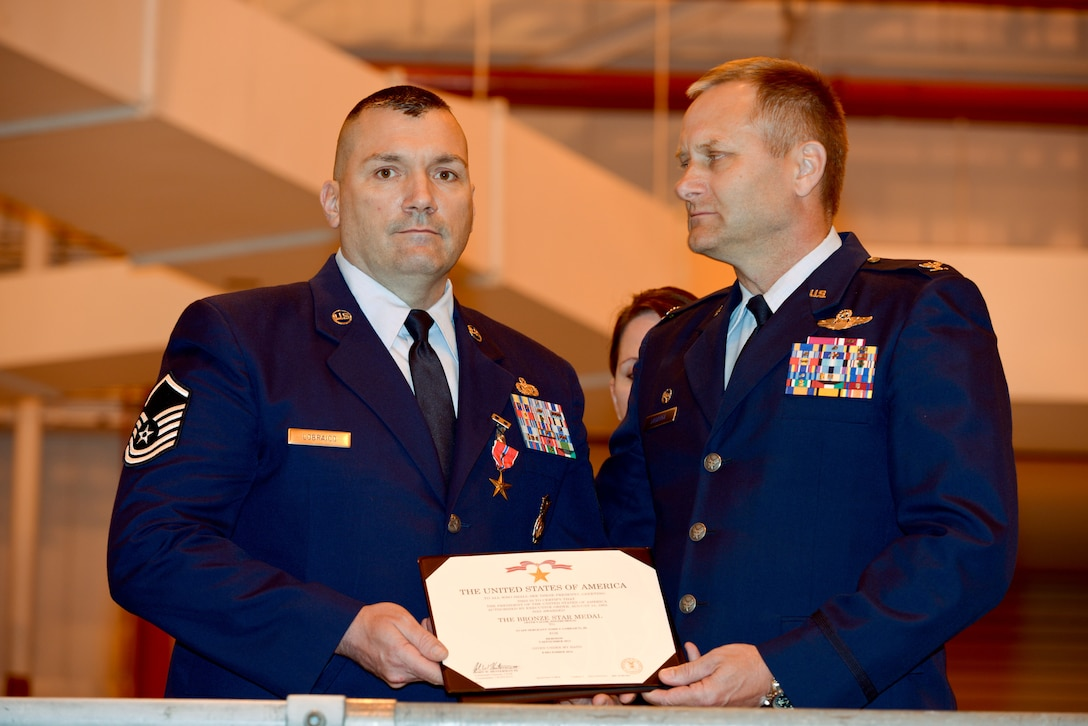"""U.S. Air Force  Master Sgt. Todd Lobraico and Col Timothy J. LaBarge, commander of the 105th Airlift Wing, New York Air National Guard, show the posthumous award of the Bronze Star Medal with Valor to his son SSgt. Todd """"T.J."""" Lobraico, during a ceremony at Stewart Air National Guard Base on April 11, 2015. Lobraico Jr., a member of the 105th Airlift Wing, was killed in action in Afghanistan on Sept. 5, 2013, (U.S. Air National Guard photo by SSgt Michael OHalloran/Released)"""