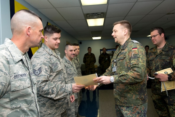 Lt. Col. Sven Henniger, commanding officer of movement and transport for the German Armed Forces Command Traffic and Transportation Division based out of Dulles International Airport, presents Staff Sgt. Jordan Soltis with the Schützenschnur, a German Armed Forces Badge for weapons proficiency. (Air National Guard photo by Master Sgt. Emily Beightol-Deyerle)