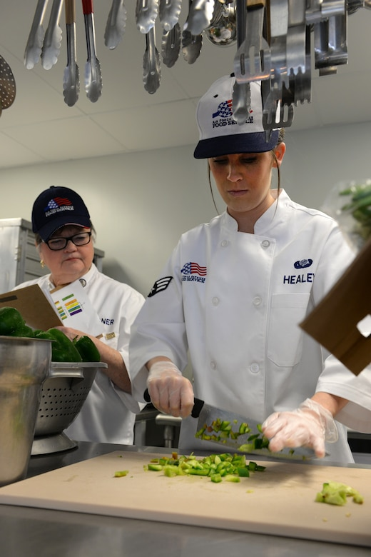 Senior Airman Nicki-Anne Healey, 157th Force Support Squadron Services Flight technician, prepares a meal under the watchful eye of a Senior Master Sergeant Kenneth Disney Award inspection team member in the Aerospace Dining Facility April 11. The 157 FSS team has been selected as one of the top three Air National Guard food services operations in the nation. Entering its 15th year, the Disney Award has been established to improve food service throughout the Air National Guard, increase morale, encourage competition, recognize excellence and honor the late Disney. Disney was the services superintendent at McGee Tyson Air Base, Tenn., for more than 20-years where he earned a reputation for commitment to providing outstanding food service. (N.H. Air National Guard photo by Senior Airman Kayla McWalter)