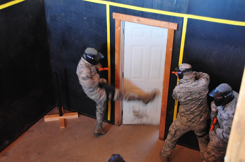 Staff Sgt. Michael Hayes breaches a door as Staff Sgt. Pablo Berchini and Staff Sgt. Nicholas Fay, members of the 161st Security Forces Squadron, prepare to clear a room inside a shoot-house during training, Phoenix, Jan. 16. Airmen practiced scenarios ranging from room clearing to entry procedures during a close quarters exercise as part of their annual training.