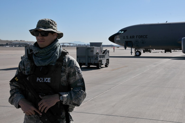"""Staff Sgt. Eric Mirabal, 161st Security Forces Squadron member, secures the perimeter and stands guard over the KC-135r tanker during a generation exercise, Phoenix Sky Harbor Air National Guard Base, April 6, 2014. This mobility exercise involves """"fast response"""" techniques in order to ensure the aircrew can react quickly and effectively when missions require a moment's notice. (Air National Guard photo by Staff Sgt. Courtney Enos)"""