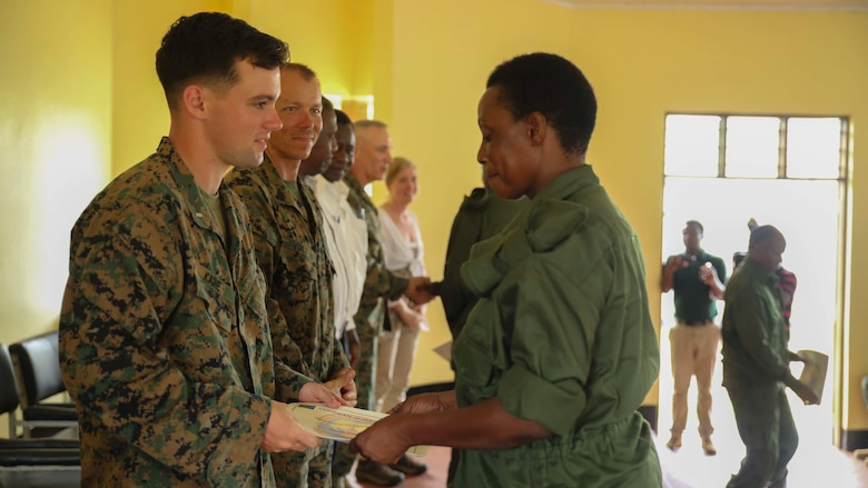 U.S. Marine 1st Lt. Nathaniel Kaine, left, the Security Cooperation Team officer-in-charge with Special-Purpose Marine Air-Ground Task Force Crisis Response Africa, hands a Tanzanian park ranger a certificate of appreciation during a graduation ceremony on the Selous Game Reserve in Matambwe, Tanzania, March 27, 2015. More than 40 Tanzanian park rangers graduated from counter illicit-trafficking training. Approximately 15 Marines and Sailors taught the park rangers infantry skills to help combat illicit trafficking.