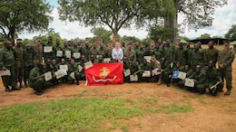 Virginia Blazer, center, the U.S. Deputy Chief of Mission to Tanzania, poses for a photo with Marines and Sailors assigned to a Security Cooperation Team with Special-Purpose Marine Air-Ground Task Force Crisis Response-Africa, and more than 40 Tanzanian park rangers following a graduation ceremony on the Selous Game Reserve in Matambwe, Tanzania, March 27, 2015. The park rangers graduated from counter illicit-trafficking training, which was the first-ever engagement between U.S. Service members and Tanzanian park rangers. The Marines and Sailors taught the park rangers infantry skills in an attempt to help counter illicit-trafficking in the region.