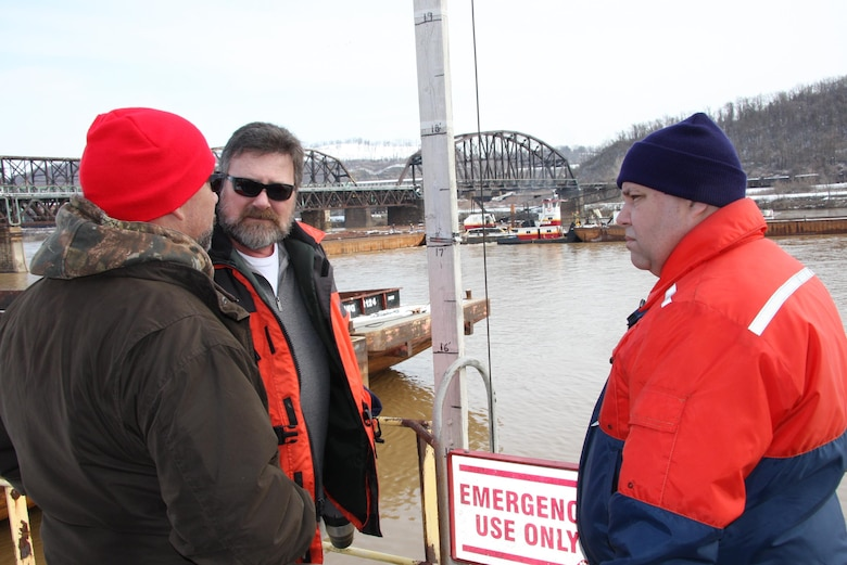 Gary Householder, (center), Mon River operations supervisor, and Mark Ivanisin, (right), Ohio River operations supervisor, speak with an unidentified man during barge recovery operations.