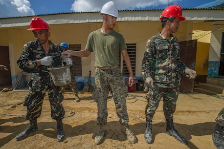 "U.S. Marine Lance Cpl. Ramon Perez, center, a civil affairs Marine assigned to III Marine Expeditionary Force, is 'shoulder-to-shoulder' with Armed Forces of the Philippines engineers from the 522nd Engineering Construction Battalion passing a bucket filled with cement for placement at Don Joaquin Elementary School in Tapaz, Philippines, during Balikatan 2015, April 9. The engineers, along with U.S. Navy Seabees from Naval Mobile Construction Battalion 5, are part of the Combined-Joint Civil-Military Operations Task Force located on the island of Panay constructing two classrooms at the school. Balikatan, which means ""shoulder to shoulder"" in Filipino, is an annual bilateral training exercise aimed at improving the ability of Philippine and U.S. military forces to work together during planning, contingency, humanitarian assistance and disaster relief operations."