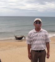 "Karl Mai stands on the same beach from which he left Vietnam in 1981 as one of the fleeing ""Boat People."" Behind him is a bamboo fishing boat like the one he and 18 others crowded into for the nighttime escape to Hong Kong. This photo was taken in August 2012 when Mai and his family revisited Vietnam."
