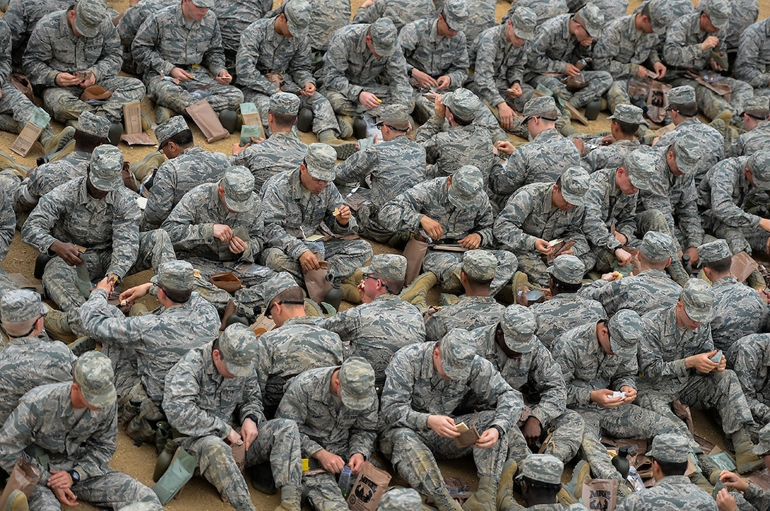"""United States Air Force basic trainees eat Meals Ready to Eat, or MREs, for lunch at the Basic Expeditionary Airman Skills Training site at Joint Base San Antonio-Lackland, Texas, April 8, 2015. Known as the """"Gateway to the Air Force,"""" all enlisted Airmen complete basic military training at Lackland, where more than 30,000 new Airmen graduate every year. (U.S. Air Force photo/Tech. Sgt. Trevor Tiernan)"""