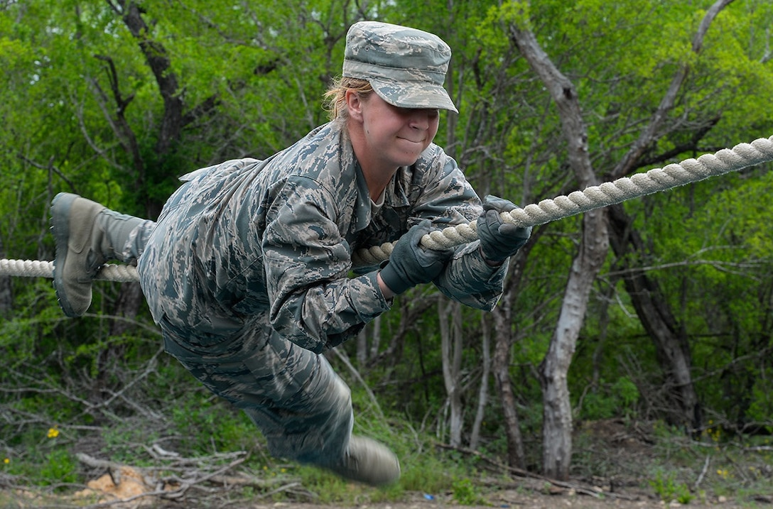 """A United States Air Force basic trainee crosses the Horizontal Rope obstacle at the Basic Expeditionary Airman Skills Training site at Joint Base San Antonio-Lackland, Texas, April 8, 2015. Known as the """"Gateway to the Air Force,"""" all enlisted Airmen complete basic military training at Lackland, where more than 30,000 new Airmen graduate every year. (U.S. Air Force photo/Tech. Sgt. Trevor Tiernan)"""