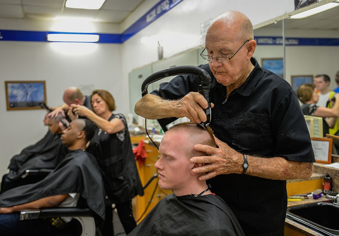 "Lester West, a barber at the Basic Military Training Processing Center barbershop, gives a new United States Air Force trainee his first Air Force haircut. Known as the ""Gateway to the Air Force,"" all enlisted Airmen complete basic military training at Lackland, where more than 30,000 new Airmen graduate every year. (U.S. Air Force photo/Tech. Sgt. Trevor Tiernan)"