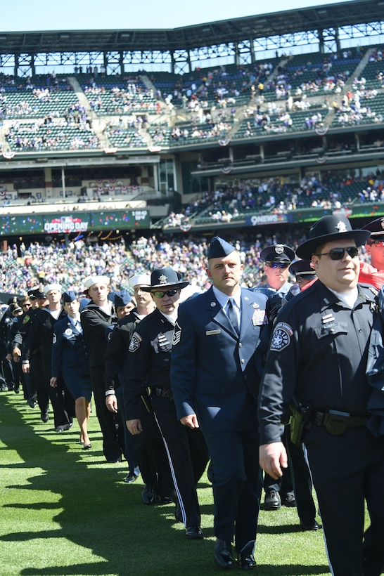 Service members and Colorado law enforcement carry the American flag off of the outfield during the Colorado Rockies Opening Day ceremony April 10, 2015, at Coors Field in Denver. Service members from all branches of service and Colorado law enforcement participated in the opening day festivities, to include an F-16 Fighting Falcon aircraft flyover and the unfurling of the American flag on the outfield. (U.S. Air Force photo by Airman 1st Class Samantha Saulsbury/Released)