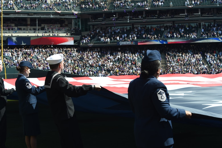 U.S. military members unfurl the American flag during the Colorado Rockies Opening Day ceremony April 10, 2015, at Coors Field in Denver. Service members from all branches of service and Colorado law enforcement participated in the opening day festivities. (U.S. Air Force photo by Airman 1st Class Samantha Saulsbury/Released)