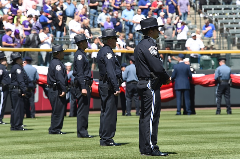 Colorado law enforcement officers and U.S. military members wait to unfurl the American flag on the outfield April 10, 2015, at Coors Field in Denver. Service members from all branches of service and Colorado law enforcement participated in the opening day festivities. (U.S. Air Force photo by Airman 1st Class Samantha Saulsbury/Released)