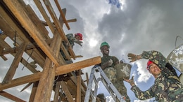 """Armed Forces of the Philippines engineers, from the 552nd Engineer Construction Battalion, U.S. Navy Seabees, assigned to Naval Mobile Construction Battalion 5, and U.S. Marine engineers, from the 9th Engineer Support Battalion, are 'shoulder-to-shoulder' as they pass buckets filled with concrete for placement at Don Joaquin Elementary School in Tapaz, Philippines, during Balikatan 2015, April 9. The engineers, part of the Combined-Joint Civil-Military Operations Task Force located on the island of Panay, are constructing two classrooms at the school. Balikatan, which means """"shoulder to shoulder"""" in Filipino, is an annual bilateral training exercise aimed at improving the ability of Philippine and U.S. military forces to work together during planning, contingency, humanitarian assistance and disaster relief operations."""