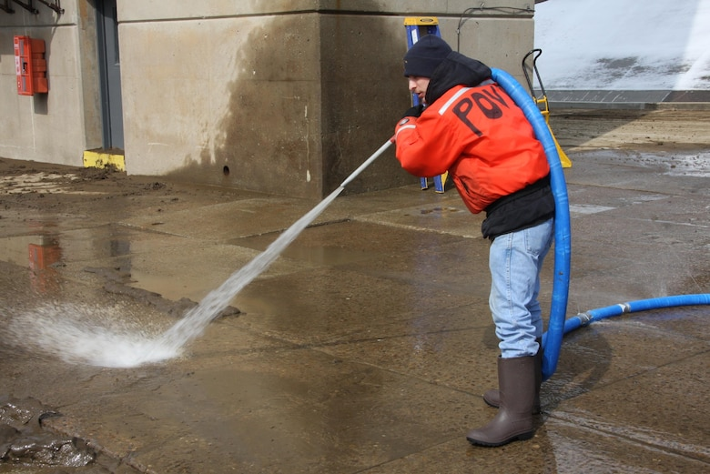 Chris Povich, lock operator, power washes the lock wall to remove mud and debris following the recent high water event at Monongahela River Locks and Dam 4 at Charleroi, March 7.