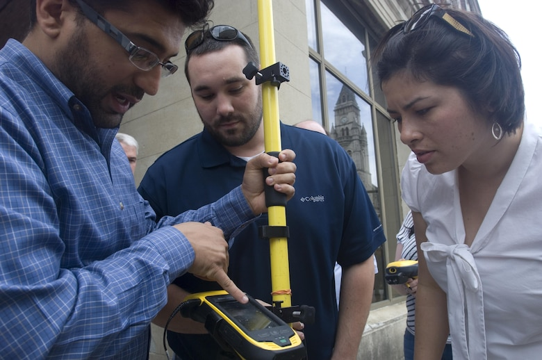 Aras Barzanji (Left), hydraulic engineer at the U.S. Army Corps of Engineers Nashville District, helps Park Rangers Dylon Anderson and Amy Redmond with a practical exercise to use a handheld GPS unit to collect data on Broadway in front of the Estes Kefauver Federal Building in Nashville, Tenn., April 9, 2015.