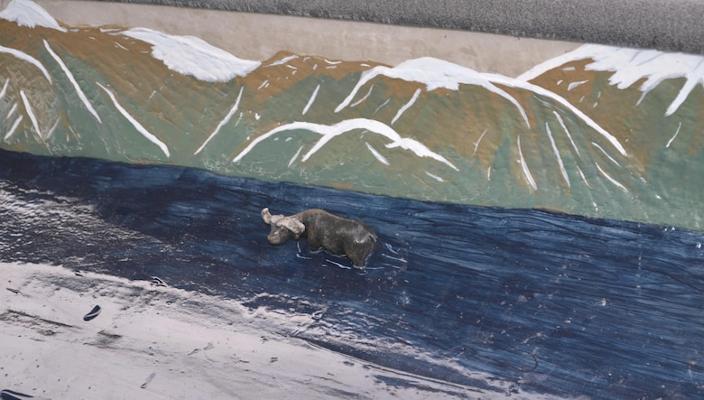 "COCHITI LAKE, N.M. -- A miniature moose figurine enjoys the ""river"" that runs inside Utah State's concrete canoe, April 11, 2015. Other animals decorating this canoe include a bear, ducks and a mountain lion. The students used cushions when racing their boat to avoid hurting themselves on the figurines."