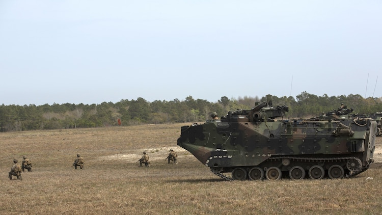 Marines with Charlie Company, 2nd Assault Amphibian Battalion, provide 360 degrees of security while Marines with Fox Company, 2nd Battalion, 2nd Marine Regiment, dismount the Assault Amphibious Vehicle aboard Marine Corps Base Camp Lejeune, North Carolina, April 9, 2015. The Marines of 2nd Bn., 2nd Marines fill in the gaps before making their way to follow-on objectives. (U.S. Marine Corps photo by Cpl. Justin T. Updegraff/ Released)