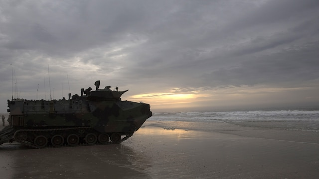 Assault amphibious vehicles sit silently on Onslow Beach aboard Marine Corps Base Camp Lejeune, North Carolina, April 8, 2015. A platoon of AAVs, filled with a company of infantry Marines from Fox Company, 2nd Battalion, embarked on the USS Wasp off the coast of Onslow Beach to prepare for the next day's mechanized infantry assault. (U.S. Marine Corps photo by Cpl. Justin T. Updegraff/ Released)
