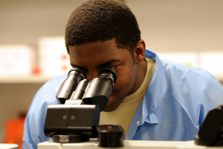 Senior Airman Roger Smith, 1st Special Operations Medical Support Squadron laboratory technician, looks at a specimen through a microscope on Hurlburt Field, Fla., April 8, 2015.  The 1st SOMDSS Laboratory is comprised of seven personnel who are responsible for more than 17,000 beneficiaries and 156,000 tests a year. (U.S. Air Force photo/Staff Sgt. Katherine Holt)