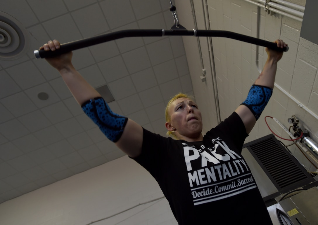 Staff Sgt. April Spilde, U.S. Air Force Honor Guard formal training instructor, exercises using the pull down machine at the West Fitness Center on Joint Base Andrews, Md., March 12, 2015.  Spilde is part of an online, powerlifting community, where she receives personalized work outs in preparation for her first official powerlifting competition.  (U.S. Air Force photo/ Senior Airman Nesha Humes)