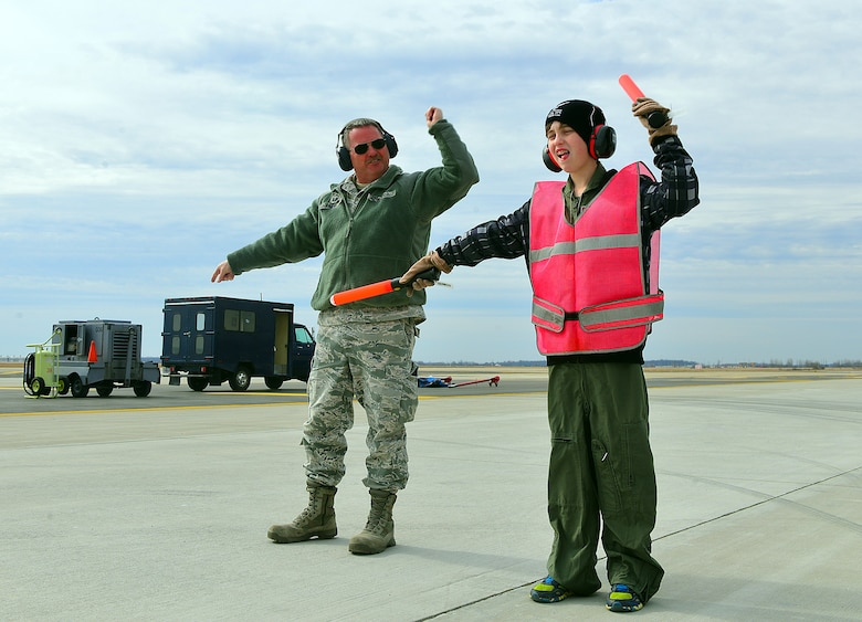 Senior Master Sgt. John Laibe, 121st Air Refueling Wing crew chief, instructs Ian Straight, a 12-year-old from Lancaster, Ohio, in the proper method of marshalling aircraft during a pilot for a day program March 19, 2015, at Rickenbacker Air National Guard Base, Ohio. The program treats a youth with chronic or life threatening illnesses to a day of military experiences. The 121st ARW has partnered with Nationwide Children's Hospital to provide this opportunity. (U.S. Air National Guard photo by Master Sgt. Ralph Branson/Released)