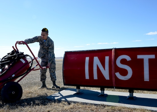 Airman 1st Class Justin Chung, 28th Operations Support Squadron airfield management coordinator, moves fire equipment off the flightline during an airfield inspection at Ellsworth Air Force Base, S.D., March 13, 2015. Airfield management personnel must ensure the airfield environment is clear of any obstructions that could pose a danger to personnel and aircraft operations. (U.S. Air Force photo by Senior Airman Anania Tekurio/Released)