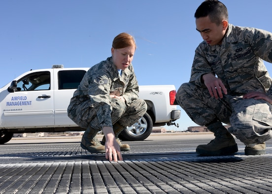 Staff Sgt. Crystal Bennoch, 28th Operations Support Squadron NCO in-charge of airfield management operations, trains Airman 1st Class Justin Chung, 28th OSS airfield management coordinator, on properly inspecting the runway centerline markings at Ellsworth Air Force Base, S.D., March 13, 2015. Airfield management personnel are responsible for inspecting airfields to ensure a safe operating environment for aircraft operations. (U.S. Air Force photo by Senior Airman Anania Tekurio/Released)