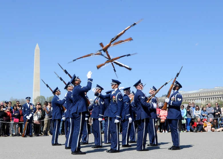 The United States Air Force Honor Guard tosses their rifles through the air during the Joint Service Drill Exhibition in Washington, D.C., April 11, 2015. The Old Guard, Army, Navy, Marines, Coast Guard and Naval Academy's drill team also performed during the event. (U.S. Air Force photo/Airman 1st Class Ryan J. Sonnier)