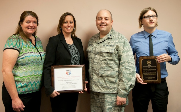 Tracy Bogdanovich, the 99th Medical Operations Squadron clinical research coordinator; Jill Clark, the 99th MDOS clinical research manager; Lt. Col. Paul Crawford, the 99th MDOS Clinical Investigation Program and Family Medicine Residency program director; and Aaron Barnett, the 99th MDOS clinical research coordinator, pose for a photo at the Mike O'Callaghan Federal Medical Center on Nellis Air Force Base, Nev., April 6, 2015. The CIP was presented with the Association of Military Surgeons of the United States 2014 Training and Education Award and the FMR was presented with the 2015 Outstanding Achievement in Scholarly Activity Award by the Uniformed Services Academy of Family Physicians. (U.S. Air Force photo/Airman 1st Class Mikaley Towle)