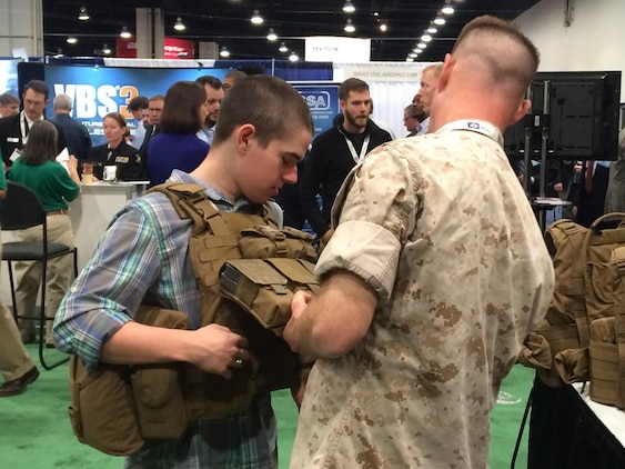 A Marine helps an attendee try on a plate carrier vest at the Gruntworks Squad Integration Facility display April 13 at the Sea-Air-Space Expo at National Harbor, Maryland. Marine Corps Systems Command's Marine Expeditionary Rifle Squad Team brought several systems and pieces of equipment to the expo to show attendees how they're working to reduce the Marine combat burden. (U.S. Marine Corps photo by Monique Randolph)