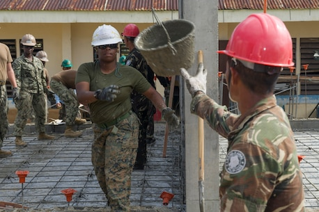 "TAPAZ, Philippines — U.S. Marine Cpl. Natauia Carpenter, assigned to the 9th Engineer Support Battalion, tosses an empty cement bucket to an Armed Forces of the Philippines Army engineer, assigned to the 552nd Engineer Construction Battalion, while constructing a concrete pad at Don Joaquin Artuz Elementary School in Tapaz, Philippines, during Balikatan 2015, April 14. The engineers are part of the Joint Civil-Military Operations Task Force on the island of Panay, which is constructing two classrooms at the school. Balikatan, which means ""shoulder to shoulder"" in Filipino, is an annual bilateral training exercise aimed at improving the ability of Philippine and U.S. military forces to work together during planning, contingency, humanitarian assistance and disaster relief operations."