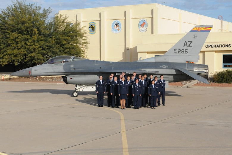 Personnel from the 162nd Wing Host Aviation Resource Management office pose for a group photo in front of one of the wing's F-16 Falcon's. The wing HARM office won the Sergeant Dee Campbell Outstanding Aviation Resource Management Large Unit of the Year award for 2014, and were presented with the award April 11 during the wing's annual awards ceremony.