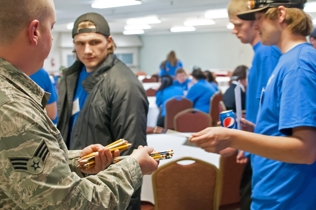 U.S. Air Force Airmen assigned to 153rd Maintenance Group, Wyoming Air National Guard, hand out test materials to students competing in the SkillsUsa competition, Apr. 13, 2015 in Casper, Wyoming. SkillsUSA Wyoming is a career-technical student organization serving students in secondary and post-secondary technical, skilled, service, and health occupations. (U.S. Air National Guard photo by Tech.Sgt John Galvin/released)