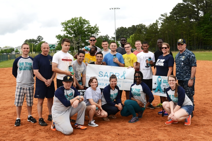 Joint Base Charleston Sexual Assault Prevention and Response team members pose with the 2015 Sexual Assault Awareness and Prevention Month kickball tournament champions at Locklear Park on Joint Base Charleston Weapons Station, April 11, 2015.  More than 30 teams and 400 players participated in the event to raise awareness of sexual assault. (U.S. Navy / Electronics Technician 2nd Class Brittany Pastrick / Released)