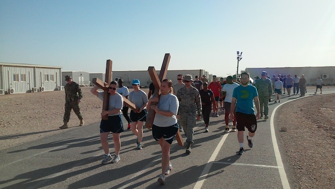 "Servicemembers carry crosses during a Good Friday ""Cross"" fit event, April 3, 2015, at Al Udeid Air Base, Qatar. During the event, several chaplains and chaplain assistants, from the Air Force, Army and Navy shared readings and prayers based on the last seven statements of Christ on the cross. After each devotion, members of the community took turns carrying three crosses for a lap around the track. (Courtesy photo)"