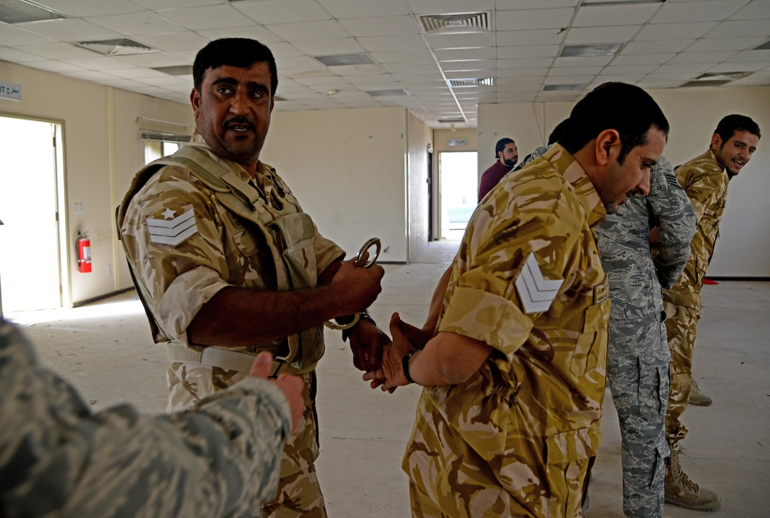 Members of the Qatar Emiri Air Force practice handcuffing techniques during joint interoperability training April 14, 2015, at Al Udeid Air Base, Qatar. Airmen from the 379th Expeditionary Security Forces Squadron shared techniques and procedures with members of the QEAF during this joint training. Training like this enhances the interoperability of both the U.S. and its host nation partners and helps improve bilateral relations by sharing techniques on how each country operates. (U.S. Air Force photo by Senior Airman Kia Atkins)