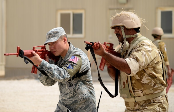 U.S. Air Force Staff Sgt. Jason Ventura, 379th Expeditionary Security Forces Squadron Check Six facilitator, demonstrates proper weapon holding procedures during joint interoperability training April 14, 2015, at Al Udeid Air Base, Qatar. Airmen from the 379th ESFS shared techniques and procedures with members of the Qatar Emiri Air Force during this joint training. Training like this enhances the interoperability of both the U.S. and its host nation partners and helps improve bilateral relations by sharing techniques on how each country operates. (U.S. Air Force photo by Senior Airman Kia Atkins)