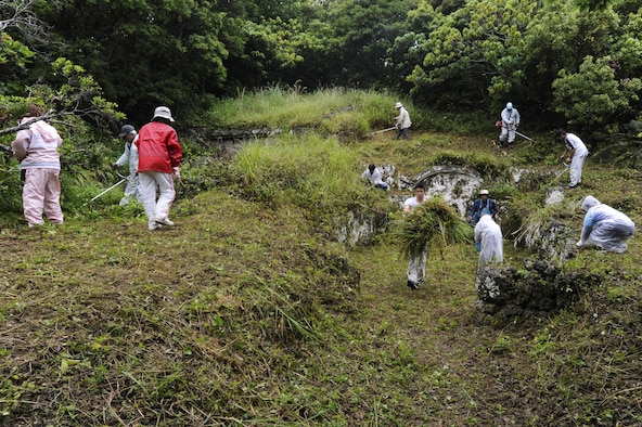 Okinawans clear overgrown plants from the area surrounding their family tomb in preparation for Shimi at Kadena Air Base, Japan, April 12, 2015. Shimi is an annual celebration on Okinawa, during which family tombs and the surrounding areas are cleaned before extended family members gather to pray and offer food to their ancestors. More than 400 locals visited the base this year to pray, eat and enjoy each other's company. (U.S. Air Force photo/Staff Sgt. Marcus Morris)