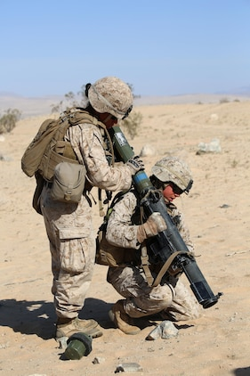 Cpl. Janelle Lopez, left, anti-tank missileman, Anti-Armor Section, Weapons Company, Ground Combat Element Integrated Task Force, loads a rocket into the MK153 shoulder-launched multipurpose assault weapon (SMAW) held by Sgt. Danielle V. Beck, right, anti-tank missileman, Anti-Armor Section, Weapons Co., GCEITF, during a Marine Corps Operational Test and Evaluation Activity assessment at Range 107, Marine Corps Air Ground Combat Center Twentynine Palms, California, April 11, 2015. From October 2014 to July 2015, the GCEITF will conduct individual and collective level skills training in designated ground combat arms occupational specialties in order to facilitate the standards-based assessment of the physical performance of Marines in a simulated operating environment performing specific ground combat arms tasks. (U.S. Marine Corps photo by Cpl. Paul S. Martinez/Released)