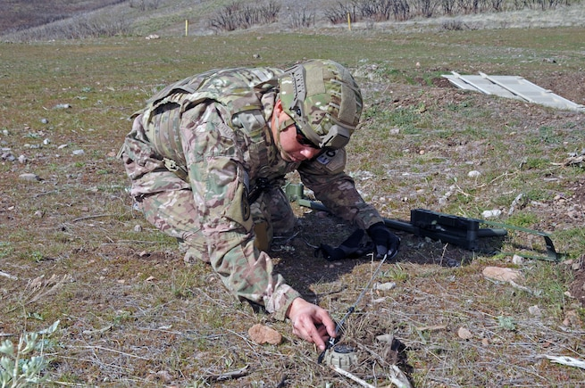 Master Sgt. Timothy Edwards, an explosive ordnance technician with the Utah Air National Guard's 151st Civil Engineering Squadron, prepares to move a simulated landmine at the Improvised Explosive Device Training Lane at Camp Williams, Utah on April 9, 2015. The training scenario conducted with the Utah Army National Guard's 1457th Engineer Battalion was followed by a discussion with Moroccan State Partners. (Air National Guard photo by Staff Sgt. Annie Edwards/RELEASED)
