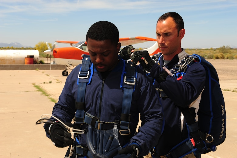 U.S. Air Force Tech. Sgt. William Howell, 98th Flying Training Squadron aircrew flight equipment specialist, preps Senior Airman Deondre Sanders, 355th Fighter Wing administrative specialist, before a tandem skydive at Desert Skydiving Center in Buckeye, Ariz., April 2, 2015. Sanders and other Airmen from Davis-Monthan Air Force Base jumped from 12,000 feet above mean sea level into a 40 second freefall. (U.S. Air Force photo by Airman 1st Class Chris Drzazgowski/Released)