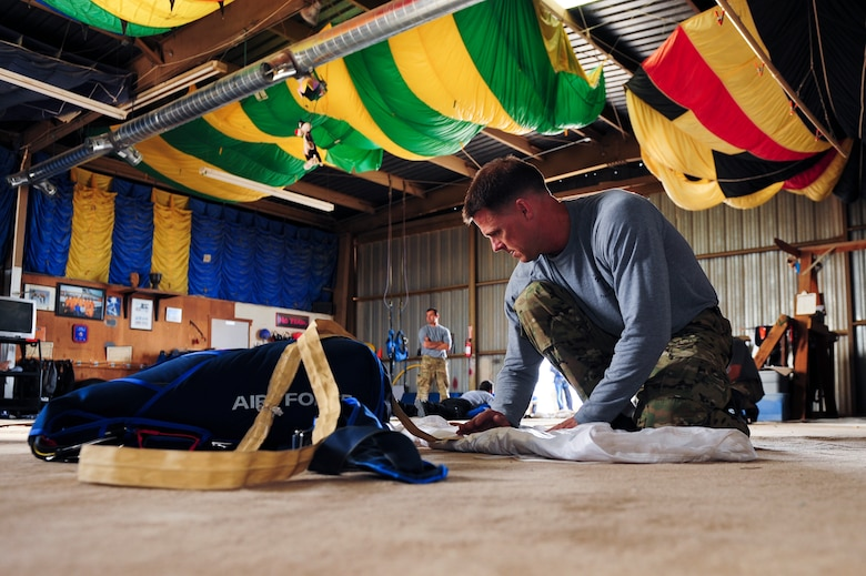 U.S. Air Force Master Sgt. Jason Nyman, 98th Flying Training Squadron parachute jump instructor, packs his parachute at Desert Skydiving Center in Buckeye, Ariz., April 2, 2015. Instructors from the 98th FTS provided Airmen from Davis-Monthan Air Force Base tandem skydiving as a way to thank D-M for its frequent accommodations in support of the squadron's mission. (U.S. Air Force photo by Airman 1st Class Chris Drzazgowski/Released)
