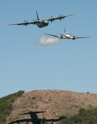 146th Airlift Wing MAFFS-equipped C-130J, California Air National Guard, follows a U.S. Forest Service lead plane smoke trail, which shows the C130 where to drop water over the Angeles National Forest, May 14, 2013. The 146th Airlift Wing held their annual Modular Airborne Firefighting Systems (MAFFS) recertification and training in partnership with U.S. Forest Service and CAL FIRE to prepare for the upcoming wildfire season. (U.S. Air National Guard photo by Staff Sgt. Nick Carzis)