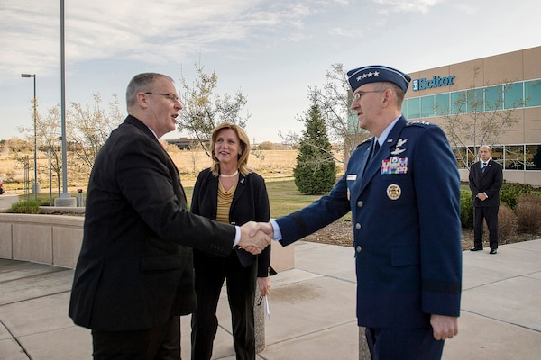 Air Force Gen. John E. Hyten, commander of Air Force Space Command, right, and Secretary of the Air Force Deborah Lee James, center, greet Deputy Defense Secretary Bob Work as he arrives at the Scitor Complex to attend and speak at the Space Symposium in Colorado Springs, Colo., April 15, 2015.